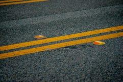 Route goudronnée noire avec les lignes jaunes et les réflecteurs oranges image libre de droits