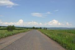 Route goudronnée par la zone verte Photographie stock