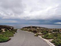 Route goudronnée par le secteur abandonné menant à la mer orageuse Photos stock