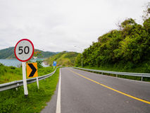 Route goudronnée sur la colline avec l'île de mer de panneau de signe de vitesse de limite à phuket Thaïlande images libres de droits
