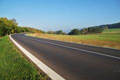 Route goudronnée vide dans la campagne, courbure de route Images stock