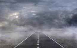 Route goudronnée dans un désert avec le ciel nuageux foncé Images stock