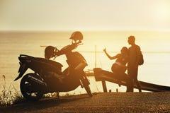 Route heureuse de moto de mer de coucher du soleil de couples Photographie stock libre de droits