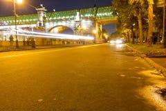 Route humide d'automne avec des lumières en parc le soir image stock