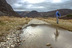 Route from Invermark to Mount Keen. Aberdeenshire, Scotland. Female hiker walking in the mountains. Route from Invermark to Mount Keen. Aberdeenshire, Scotland royalty free stock image
