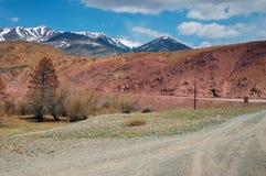 Route, montagnes rouges et cieux bleus Photographie stock