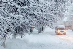 Route neigeuse d'hiver avec la voiture près des bâtiments Photos libres de droits