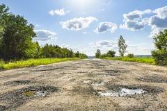 Route, nids de poule et puits cassés photographie stock