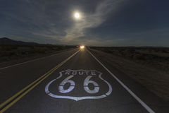 Route 66 Night Moon with Headlights. Route 66 sign with full moon and oncoming headlights in the California Mojave desert Royalty Free Stock Photo