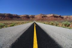 Route noire et signalisation horizontale jaune en montagnes Photos libres de droits