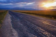 Route, nuages et coucher du soleil vides Photos libres de droits