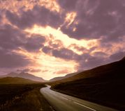 Route par le coucher du soleil de montagnes   photos stock