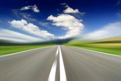 Route parmi les champs verts avec l'effet de tache floue de mouvement photos stock