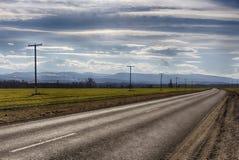 Route pavée dans le paysage de ressort de montagnes Photographie stock libre de droits