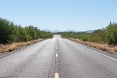 Route pavée en avant par le désert avec des montagnes à l'arrière-plan photographie stock libre de droits