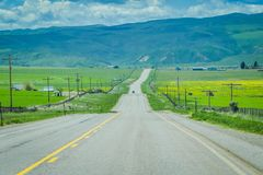 Route pavée en parc national de Yellowstone, Wyoming, Etats-Unis, entre les prairies, les montagnes et le ciel nuageux Photos stock
