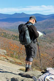 The Route Planner. A man stops to look at a map and plan a hiking route in the White Mountains of New Hampshire Royalty Free Stock Photography