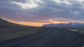 Route rurale menant dans un coucher du soleil orange Photographie stock
