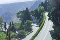 Route serpentine sinueuse en montagnes vertes - beau panorama de Taormina, Sicile photos stock