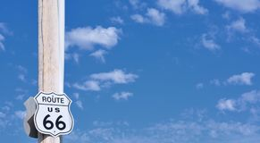 Route 66 sign on blue sky with clouds. Route 66 sign on blue sky background stock photo