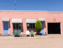 Route 66 Spanish architecture . New Mexico, USA. Concrete stucco exterior in pink with blue doors and retro chairs outside Spanish influenced architecture Route stock photo