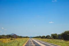 Route sud-africaine par les savannas et les déserts avec l'inscription photos stock