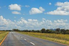 Route sud-africaine par les savannas et les déserts avec l'inscription photo libre de droits
