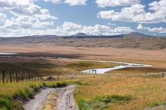 Route suivant la ligne de frontière sur un plateau des montagnes de montagne avec l'herbe verte au fond de la vallée White River Image libre de droits