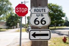 Route 66 tecken med pil- och stopptecknet Arkivbild