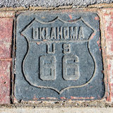 Route 66: US 66 Shield, Tulsa, OK. This colorful Route 66 shield is stamped in concrete, poured between decorative bricks, on the Tulsa sidewalk, Oklahoma Stock Photos