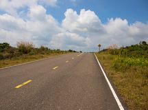Route vide au ciel nuageux Route droite en collines vertes Bord de la route tropical Tournez le bon signe Images libres de droits