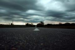 Route vide de campagne sous le ciel orageux Photographie stock libre de droits