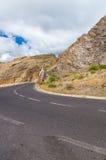 Route vide et panneau d'avertissement en baisse de roches Image libre de droits