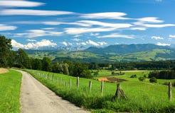 Route, vieille frontière de sécurité le long de elle, zones vertes et mountai Photo stock