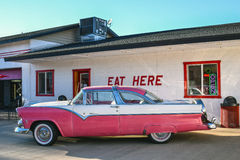 Route 66, Williams, old-timer car. WILLIAMS, ARIZONA, USA – MARCH 21, 2016: Pink old-timer car in front of a cafe in Williams, on the historic Route 66. The Stock Image