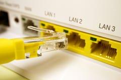 Router bianco per Internet domestico con i porti gialli per gli abbonati da cui il cavo di toppa giallo fotografia stock libera da diritti