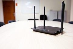 Router preto com as quatro antenas para o wifi em uma tabela de madeira clara fotografia de stock royalty free