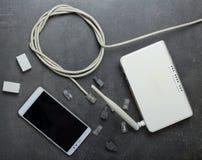Routeur et câble de Wi-Fi pour la connexion, les connecteurs, les adaptateurs et le smartphone sur le gris images libres de droits