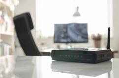 Routeur sans fil noir sur la table réfléchie blanche Photographie stock