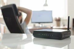 Routeur sans fil noir sur la table réfléchie blanche Images stock