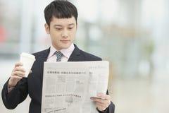Routine de matin de jeune café se tenant et potable d'homme d'affaires et lisant le journal images stock