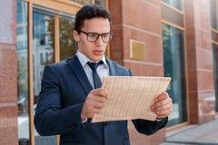 Routine de matin Homme d'affaires dans des lunettes se tenant sur la rue de ville regardant le plan rapproché choqué par journal image libre de droits