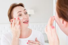 Routine de matin Regarder femelle dans le miroir la chambre à coucher Beau visage de femme de Moyen Âge avec la base cosmétique s photo stock