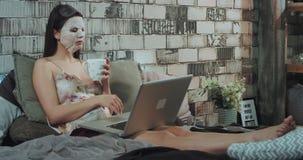 Routine di bellezza di mattina per una donna di affari che sdraia sul letto con una maschera di protezioni sul lavorare al suo at stock footage