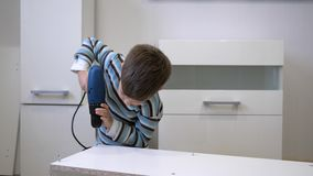 Routine domestiche del bambino, bambino abile con il trapano elettrico durante il montaggio di mobilia di legno nella sala video d archivio