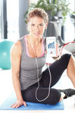 Daily routine at fitness. Portrait of sporty woman sitting at fitness center after workout. Smiling female holding holding in hand her smartphone and and using Stock Photos