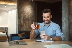 Routine quotidienne d'homme de célibataire fonctionnant du smartphone potable de lecture rapide de thé de concept simple à la mai images libres de droits