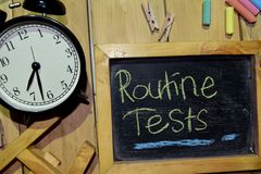 Routine Tests on phrase colorful handwritten on chalkboard. And alarm clock with motivation, inspiration and education concepts. Table background stock photo