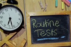 Routine Tests on phrase colorful handwritten on chalkboard. And alarm clock with motivation, inspiration and education concepts. Table background stock photography