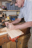 Routing plane carpentry. Man using routing plane on workbench with tools and odds and ends in background Stock Images